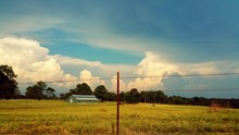 Barn On Field With Barbed Wire Fence Against Sky