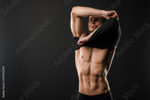 Fototapeta Muscular athletic man taking off t-shirt with copy space obraz