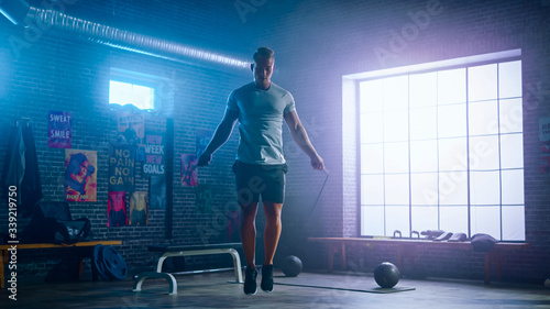 Valokuva Masculine Athletic Young Man Exercises with Jumping Rope in a Loft Style Industrial Gym