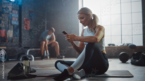 Fényképezés Happy and Smiling Beautiful Athletic Young Woman is Using a Smartphone while Sitting on a Floor in a Loft Gym
