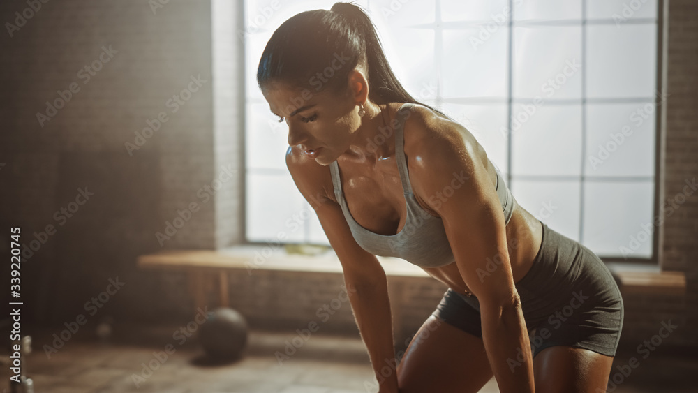 Fototapeta Portrait of a Beautiful Strong Fit Brunette Wiping Sweat from Her Face in a Loft Industrial Gym with Motivational Posters. She's Catching Her Breath after Intense Fitness Training Workout. Warm Light.