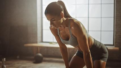 Portret lijepe snažne brinete brišući znoj s lica u potkrovlju, industrijska teretana s motivacijskim plakatima. Hvata svoj dah nakon intenzivnog treninga u fitnes treningu. Topla svjetlost.