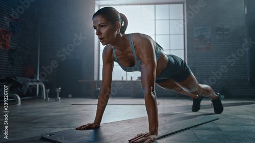 Fototapeta Strong and Fit Athletic Woman in Sport Top and Shorts is Doing Push Up Exercises in a Loft Style Industrial Gym with Motivational Posters. It's Part of Her Cross Fitness Training Workout.