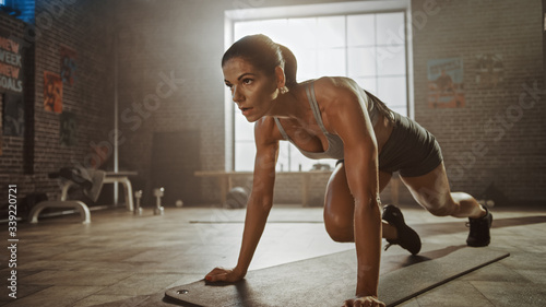 Obraz na płótnie Strong and Fit Athletic Woman in Sport Top and Shorts is Doing Mountain Climber Exercises in a Loft Style Industrial Gym with Motivational Posters
