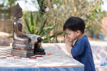 A Cute Little Asian Boy Wearing A Blue Shirt Paying Respect To A Buddha Image And Bathing A Buddha Image On Songkran Festival. Chiang Mai, Thailand