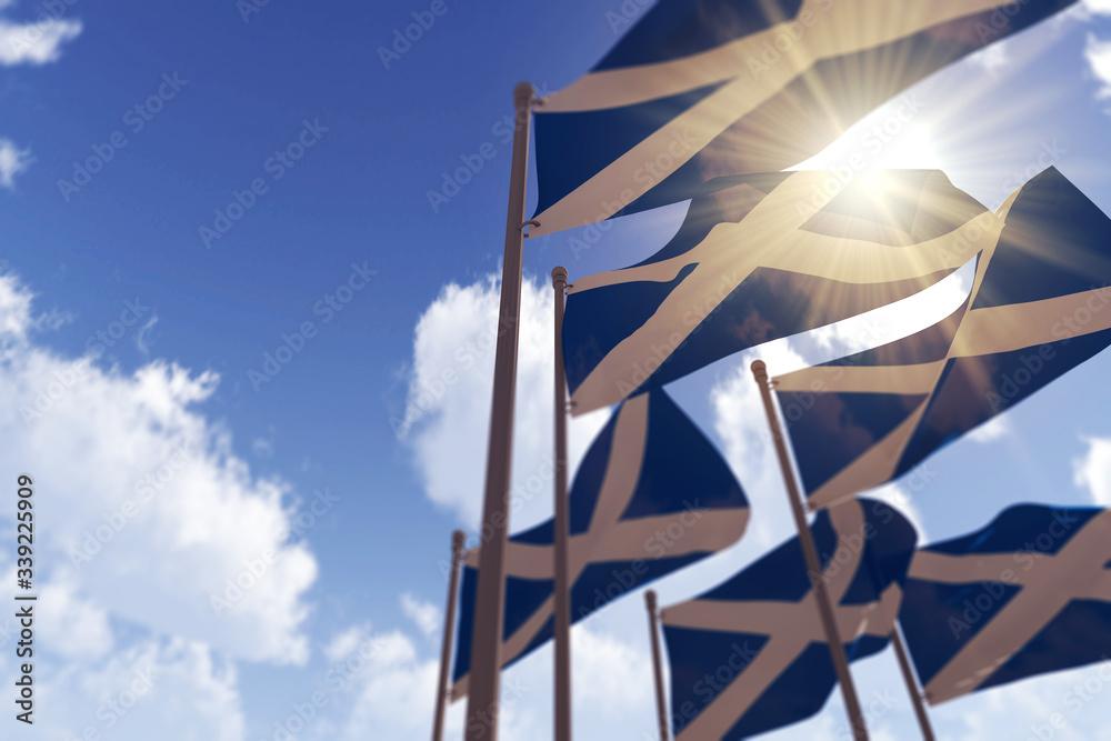 Fototapeta Scotland flags waving in the wind against a blue sky. 3D Rendering