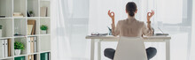 Panoramic Shot Of Businesswoman Meditating In Lotus Pose With Gyan Mudra At Workplace With Incense Stick