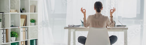 Fotografía panoramic shot of businesswoman meditating in lotus pose with gyan mudra at work