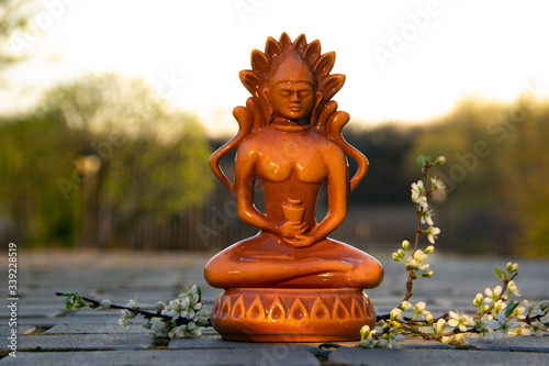 Photo A small Buddha statue stands on a brick walkway with a blossoming wind tree
