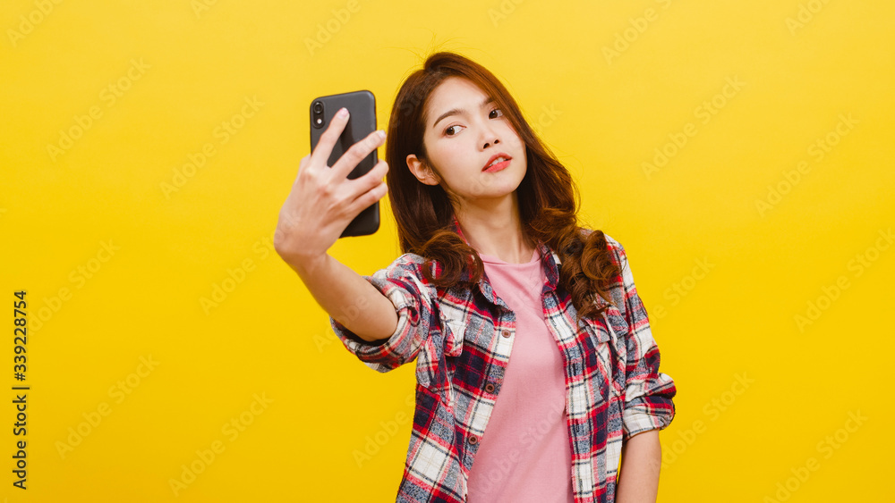 Fototapeta Smiling adorable Asian female making selfie photo on smartphone with positive expression in casual clothing and looking at camera over yellow background. Happy adorable glad woman rejoices success.
