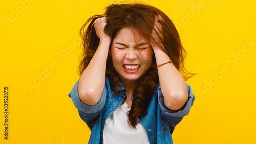Fotomural Portrait of young Asian lady with negative expression, excited screaming, crying emotional angry in casual clothing and looking at the camera over yellow background