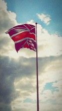Red Union Jack Flag Waving Against Cloudy Sky