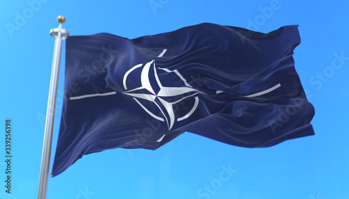 NATO flag waving at wind in slow in blue sky Canvas Print