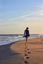 The Woman Is Walking Along The Sea Beach. Traces On The Sand