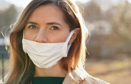 Fotografie, Obraz Young woman wears home made white cotton virus mouth face mask, wrong way, incor