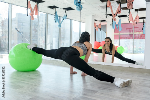 Photo Beautiful young woman doing strenght exercise on fit ball in aerobics class stud