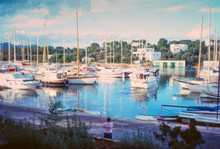 Rear View Of Person Standing By Moored Sailboats On Harbor Against Sky