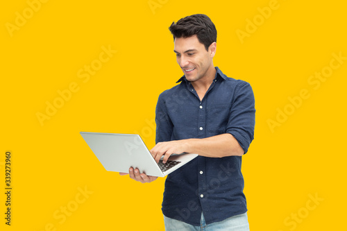 Obraz Portrait of an excited man holding laptop computer isolated on yellow background, Feeling happiness, Caucasian Male model - fototapety do salonu