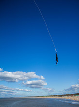 Person Performing Bungee Jump Against Blue Sky