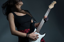 Beautiful Girl Emotionally Plays The Electric Guitar. Studio Photo On A Gray Background. Rock And Roll Girl In Dark Clothes Plays Heavy Metal Guitar Riffs