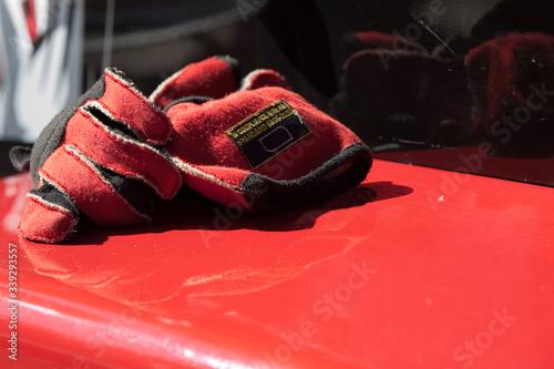 Gants rouges posés sur une voiture de course Canvas-taulu