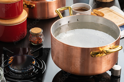 Fényképezés Copper pot with boiling water on a gas stove close up