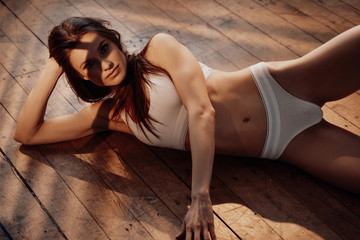 Stylish and smooth young female model with dark hair and sporty underwear posing while laying on a wooden floor in a bright room filled with sunlight, looking daring and erotic