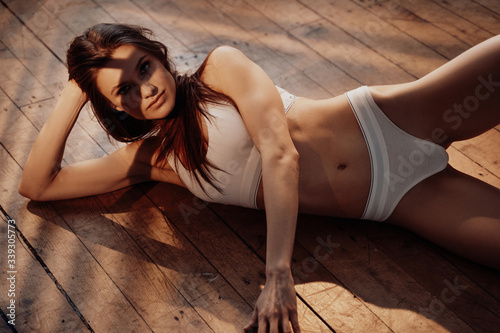 Fototapeta Stylish and smooth young female model with dark hair and sporty underwear posing while laying on a wooden floor in a bright room filled with sunlight, looking daring and erotic obraz