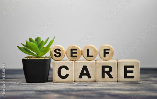 Photo SELF CARE - text on wooden cubes, green plant in black pot on a wooden backgroun