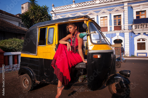 Fényképezés girl in the  of the Indian city in, a red dress posing on the background of an auto rickshaw