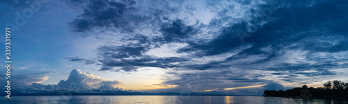 Photo Sunset Cloud Formations over Mountainous Area with View of Calm Ocean