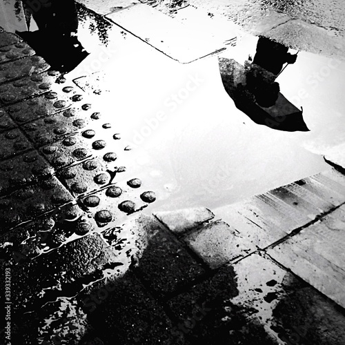 Photo Person Reflecting In Puddle On Street During Monsoon