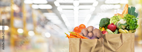 Fototapeta Eco friendly reusable shopping bags filled with bread, fruits and vegetables on a supermarket background obraz