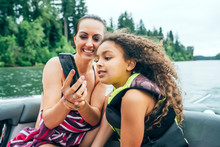 Smiling Mom Showing Daughter Video On Smart Phone On Boat On Lake Surrounded By Trees