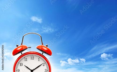 Obraz Red alarm clock on blue sky background. - fototapety do salonu