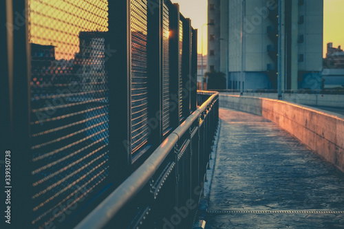 Canvas Print Footbridge By Chainlink Fence In City