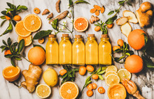 Immune Boosting Vitamin Health Defending Drink. Flat-lay Of Fresh Turmeric, Ginger, Citrus Juice Shot In Glass Bottles Over Marble Background, Top View. Vegan Immunity System Booster