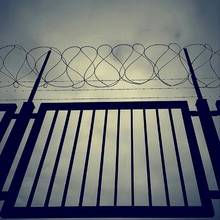 Low Angle View Of Gate With Barbed And Concertina Wire Against The Sky