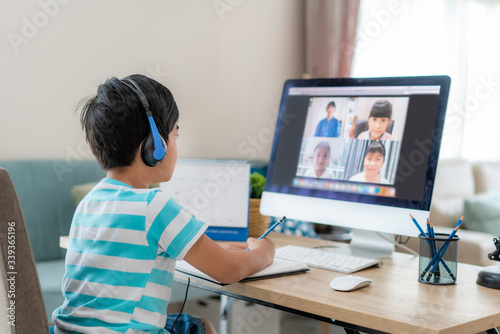 Fényképezés Asian boy student video conference e-learning with teacher and classmates on computer in living room at home