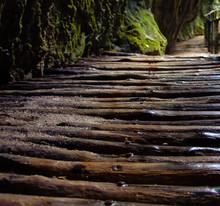 Wet Wooden Walkway By Rocks