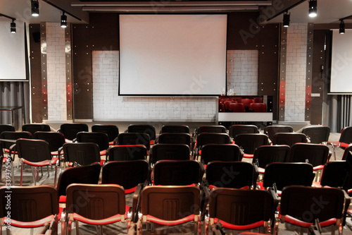 lecture hall / conference room with red chairs and screen Canvas Print