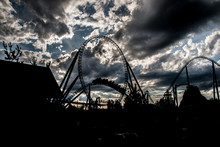 Low Angle View Of Silhouette Rollercoaster Against Cloudy Sky