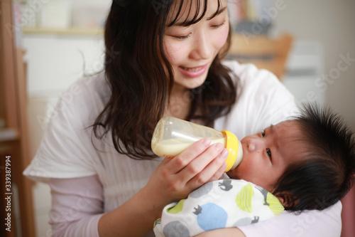 Photo 赤ちゃんにミルクを与える母親
