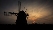 Silhouette Traditional Windmill On Field Against Sky At Sunset