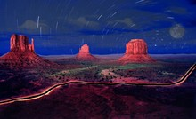 Scenic View Of Monument Valley Tribal Park Against Star Trails At Night