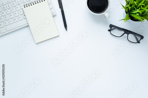 Fototapeta Workplace in office with white desk. Top view from above of keyboard with notebook and coffee. Space for modern creative work of designer. Flat lay with blank copy space. Business and finance concept. obraz na płótnie