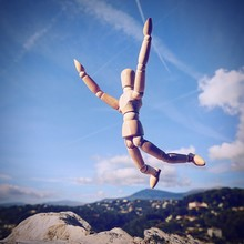 Low Angle View Of Wooden Mannequin Against Blue Sky