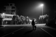 Silhouette Person Walking With Dog On Street At Night