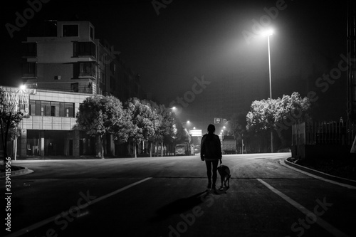 Silhouette Person Walking With Dog On Street At Night - fototapety na wymiar