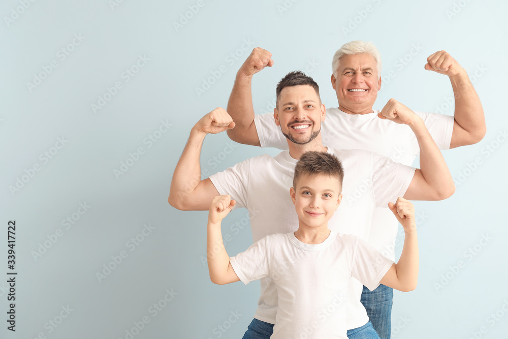 Fototapeta Man with his father and son showing muscles on color background